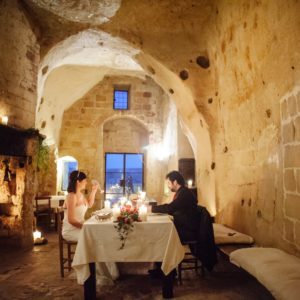 Coppia che cena in una chiesa sconsacrata nelle grotte tra i Sassi di Matera